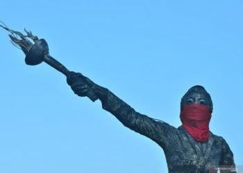 PATUNG KARTINI DI PASANG MASKER. Patung Raden Ajeng Kartini dipasangi masker di Jepara, Jawa Tengah, Rabu (1/7). Patung yang menjadi simbol kota Jepara tersebut dipasangi masker guna mensosialisasikan pada warga untuk meningkatkan kesadaran mengenakan masker menyusul lonjakan tajam kasus terkonfirmasi positif COVID-19 di wilayah itu dari yang semula lima kasus menjadi 398 kasus positif dalam waktu lima pekan dan 27 orang diantaranya meninggal dunia.  ANTARA FOTO/Yusuf Nugroho