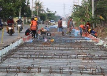 RIGID BETON. Para pekerja membuat anyaman besi untuk dasaran rigid beton Jalan Pangeran Senopati Harapanjaya, Sukarame, Bandar Lampung, Minggu (22/11). Jalan tersebut menjadi alternatif menuju pintu tol Itera Kotabaru, Lampung Selatan.  n LAMPUNG POST/SUKISNO