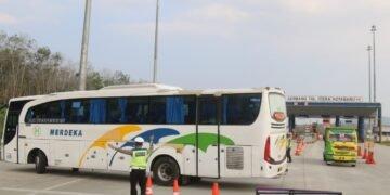 Anggota Ditlantas Polda Lampung memutar balik bus luar Lampung yang hendak memasuki Kota Bandar Lampung di posko penyekatan PPKM gerbang tol Itera, Kotabaru, Lampung Selatan saat pembatasan kegiatan masyarakat (PPKM) darurat di Kota Bandar Lampung, Minggu (18/7). (LAMPUNG POST/SUKISNO)